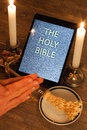 The holy bible in tablet computer digital as a symbol of a new era scene from cross candles and sprinkler and hands folded prayer Royalty Free Stock Photo