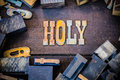 Holy concept rusty type the word written in rusted metal letters surrounded by vintage wooden and metal letterpress Royalty Free Stock Photography