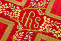 Holy ihs on vestment closeup of antique th century chasuble with the letters iesus hominum salvator which means name of jesus in Royalty Free Stock Photo