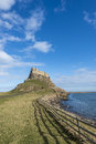 Holy island castle in portrait against a blue sky Stock Images