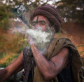 Holy man smoking pipe at bank of ganga river Stock Image