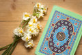 Holy Quran book and daffodils on the wooden background. Ramadan Royalty Free Stock Photo