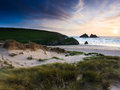 Holywell bay cornwall the sun setting over beach viewed from the sand dunes england uk Stock Photo