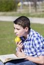 Hombre de looking young que lee un libro en al aire libre con la manzana amarilla Imagenes de archivo