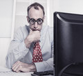 Hombre de negocios con exceso de trabajo con los vidrios que mira fijamente en espacio el escritorio Fotografía de archivo