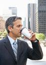 Hombre de negocios drinking takeaway coffee fuera de la oficina Imagenes de archivo