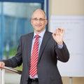 Hombre de negocios gesturing ok sign en oficina Imágenes de archivo libres de regalías