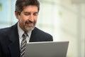 Hombre de negocios hispánico using laptop Fotos de archivo