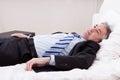 Hombre de negocios relaxing on bed Foto de archivo libre de regalías