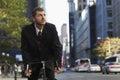 Hombre de negocios riding bicycle while que mira lejos Imágenes de archivo libres de regalías