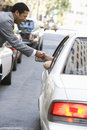 Hombre de negocios shaking hand with person in car Fotografía de archivo libre de regalías