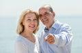Hombre en la playa que muestra a la mano algo a su mujer Fotos de archivo