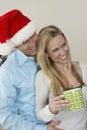 Hombre en taza de café de santa hat embracing woman holding Imagenes de archivo