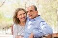Hombre envejecido y mujer que abrazan en un banco Fotos de archivo