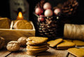 Home baked Christmas gingerbread pepper cookies stacked, in wood box. Colorful baubles, pine cones in basket. Lit candle Royalty Free Stock Photo