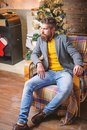 Home is best place. Man bearded hipster relax sit armchair near christmas tree. Feel like home. Man mature confident guy Royalty Free Stock Photo