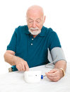 Home blood pressure check senior man checking his at isolated on white Stock Image
