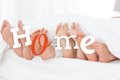 Home comcept message on image of familys feet sticking out from under bed covers Stock Images
