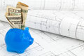 Home construction financing blue piggybank with dollar bills on plans building concept Royalty Free Stock Photography