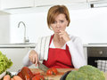 Home cook woman in red apron slicing carrot with kitchen knife suffering domestic accident cutting hurting finger Royalty Free Stock Photo