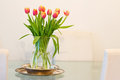 Home decoration: vase of tulips on glass table Royalty Free Stock Image