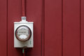 Home electric meter grey energy on red painted exterior wall Stock Photography
