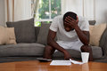 Home finance debt man disapointed troubled african black sitting on sofa couch calculating bill in living room Royalty Free Stock Images