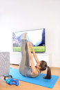 Home fitness ab workout in front of television girl doing toe touch exercises to train upper abs while watching a nature tv show Stock Image