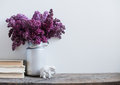 Home interior decor bouquet of lilacs in a vase and books on rustic wooden table on a white wall background Royalty Free Stock Photo