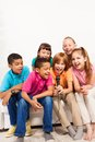 Home karaoke group of happy kids boys and girls singing on together sitting on the coach in living room Royalty Free Stock Image