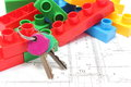 Home keys and building blocks on housing plan closeup of heap of colorful lying construction drawing of house for children Royalty Free Stock Photography