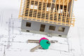 Home keys and small house under construction on electrical drawings, building home concept Royalty Free Stock Photo