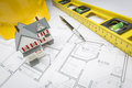 Home, Level, Hard Hat and Pencil Resting on House Plans Royalty Free Stock Photo