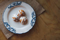 Home made choux cream on white plate. Over on wood table. Top view. with a white glaze. on wooden background Royalty Free Stock Photo