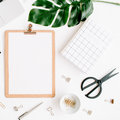 Home office workspace mockup with laptop, clipboard, palm leaf, notebook and accessories Royalty Free Stock Photo