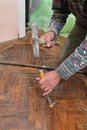 Home renovation worker cut old parquet floor with chisel and hammer Royalty Free Stock Photos