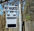 Home for sale sign board text not haunted and in uppercase letters on a two part placed at the gate of a house which is on the Royalty Free Stock Image