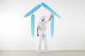 Home service concept. painter man with brush drawing a blue house Royalty Free Stock Photo