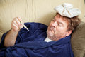 Home sick from work man in his bathrobe on the couch he has an icepack on his head and is taking his temperature Stock Photo