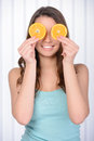 Home spa funny girl portrait holding oranges over eyes conceptual image of healthy eating dieting skincare Stock Photography