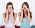 Home spa two beautiful young women holding pieces of cucumber on their eyes and smiling while sitting on the bed Royalty Free Stock Image
