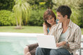 Home Tech Couple with Laptop by Swimming Pool Royalty Free Stock Photography