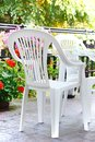 Home terrace white plastic chairs and table on the in the garden Royalty Free Stock Image