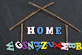HOME word on black board background composed from colorful abc alphabet block wooden letters, copy space for ad text