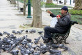 Homeless amn man sharing his meal with birds picture taken on the road rua da liberdade in lisbon portugal in april Stock Photography