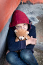 Homeless boy leaned against the wall with bear young Royalty Free Stock Image