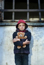 Homeless boy leaned against the wall with bear young Royalty Free Stock Photo
