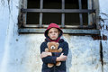Homeless boy leaned against the wall with bear young Royalty Free Stock Photography