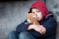 Homeless boy leaned against the wall with bear young Royalty Free Stock Photos