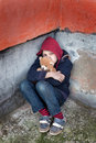Homeless boy leaned against the wall with bear young Stock Photo